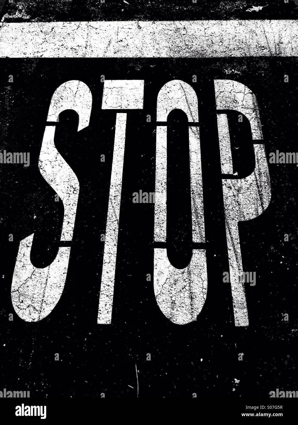 Stop sign on pavement in black and white - Stock Image