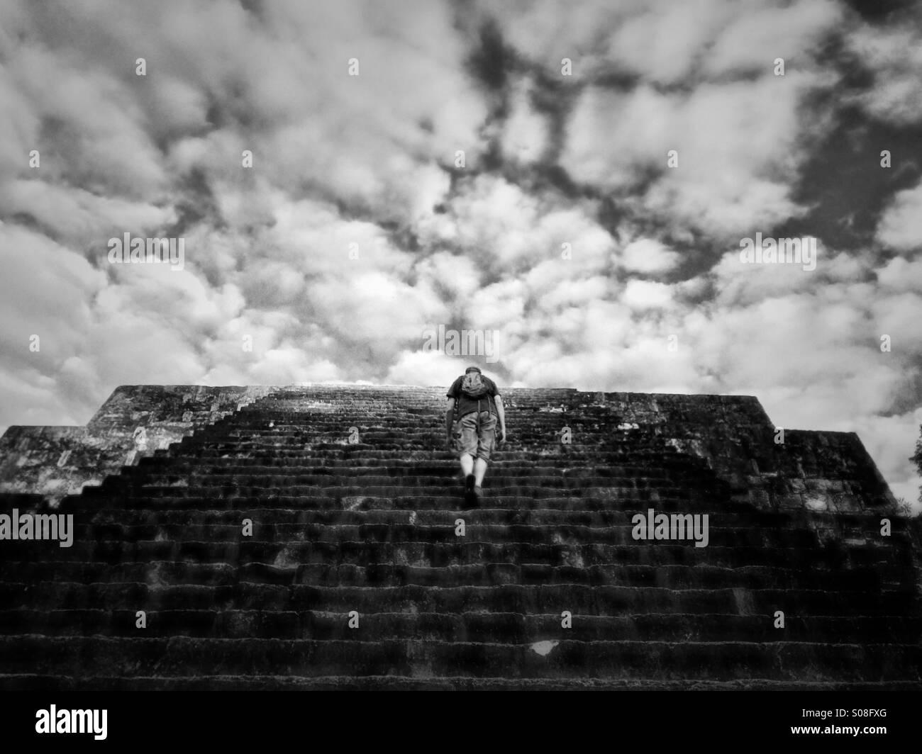 Man climbing pyramid at Tikal, Guatemala - Stock Image