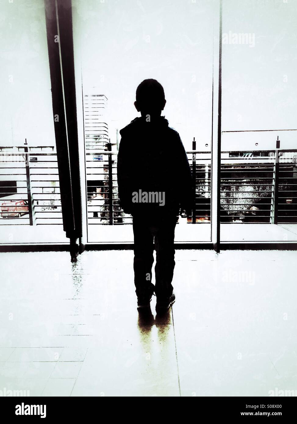 Boy standing inside a building - Stock Image