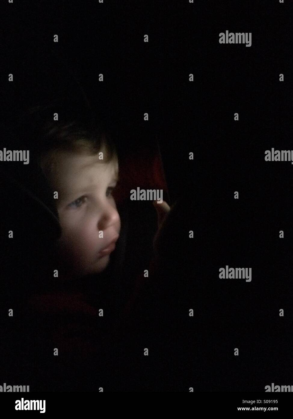 Child looking through the dark - Stock Image
