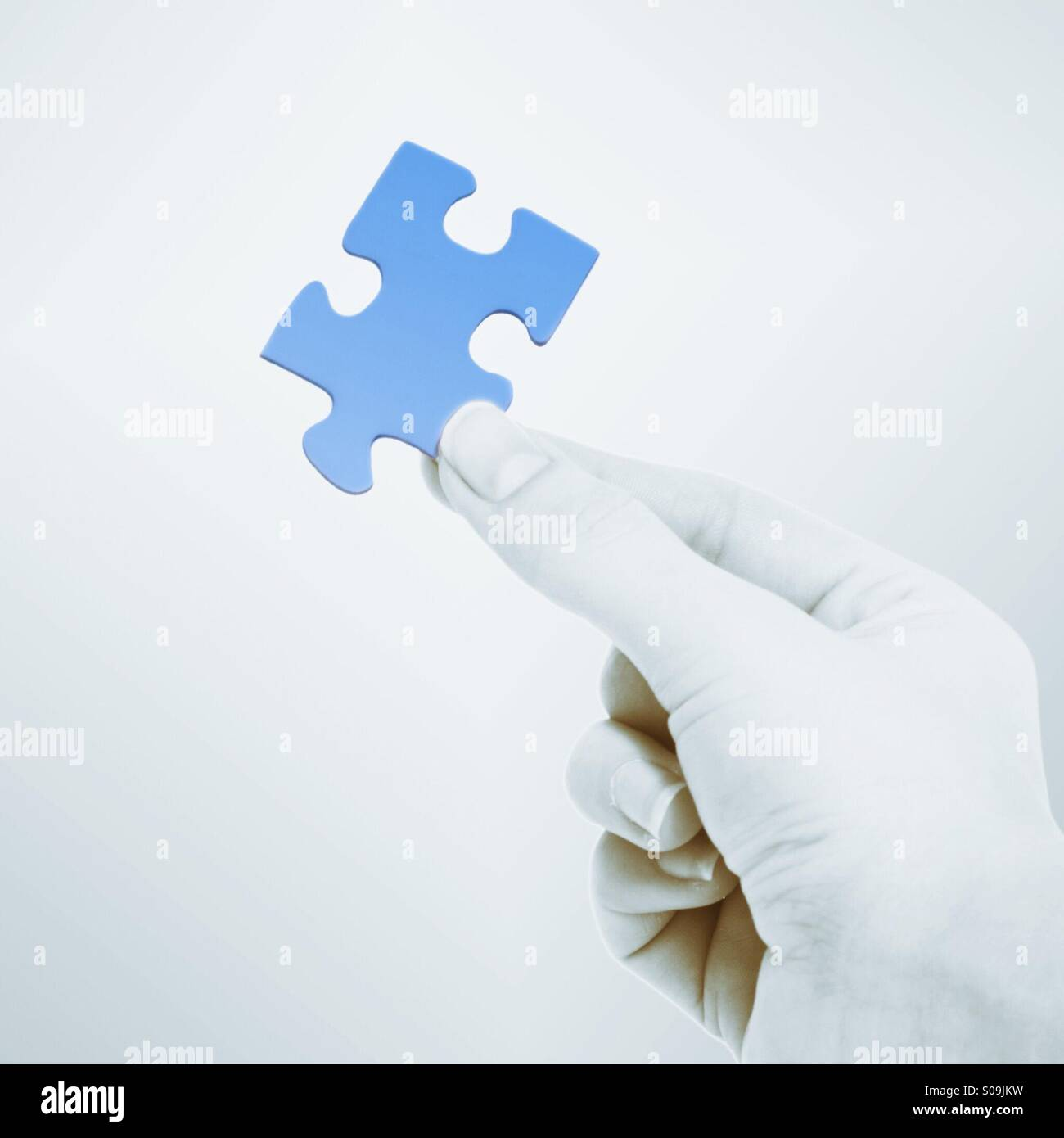 Hand holding piece of jigsaw puzzle - Stock Image