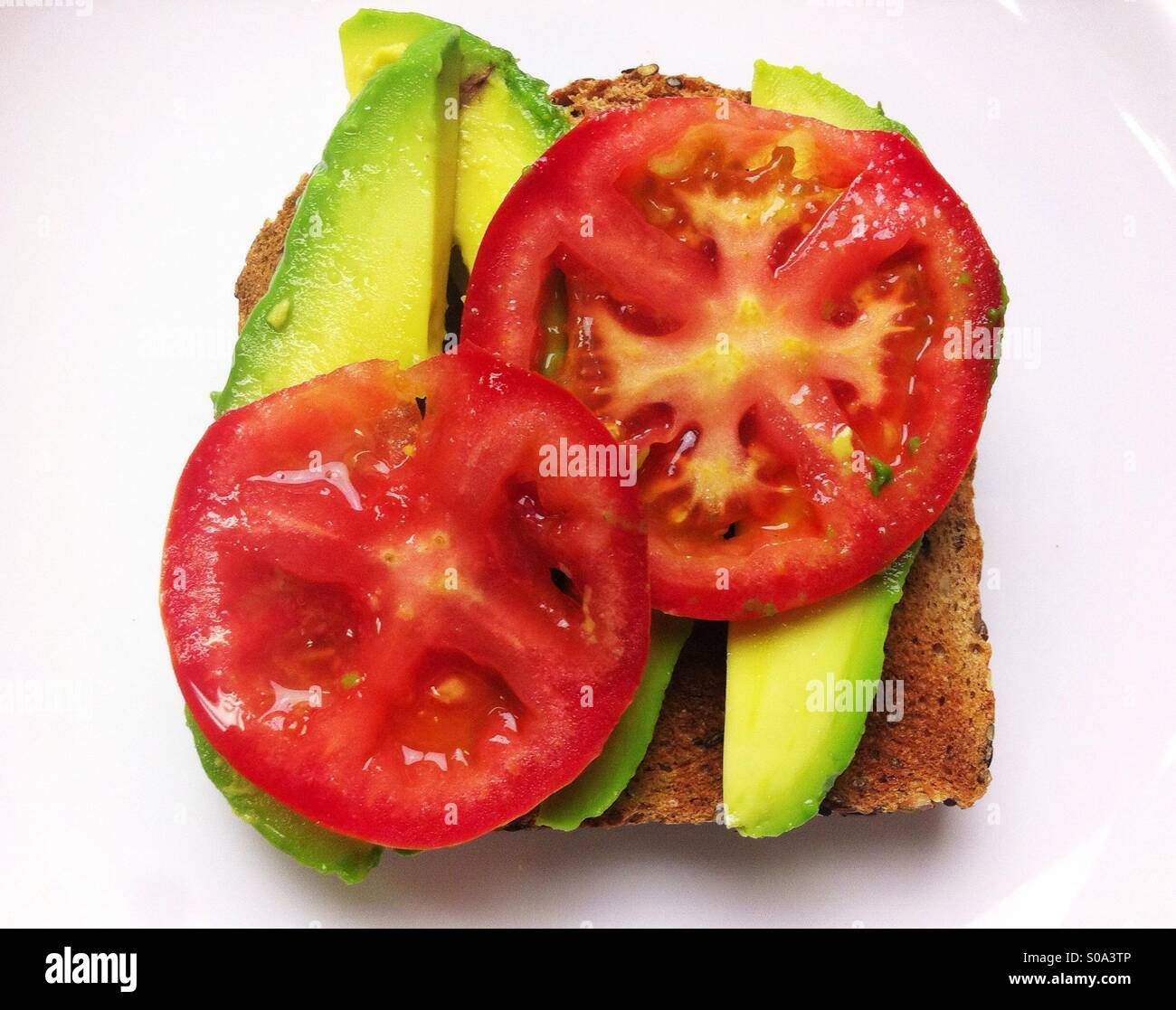 Open vegetable sandwich on whole wheat bread with avocado and tomato - Stock Image