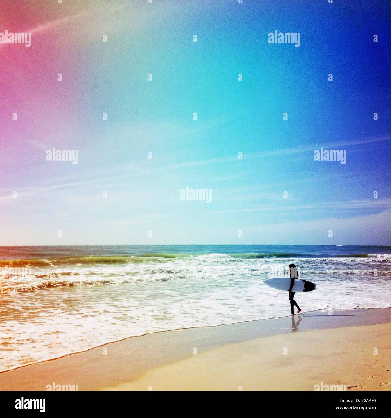 Surfer going into the ocean to surf. - Stock Image