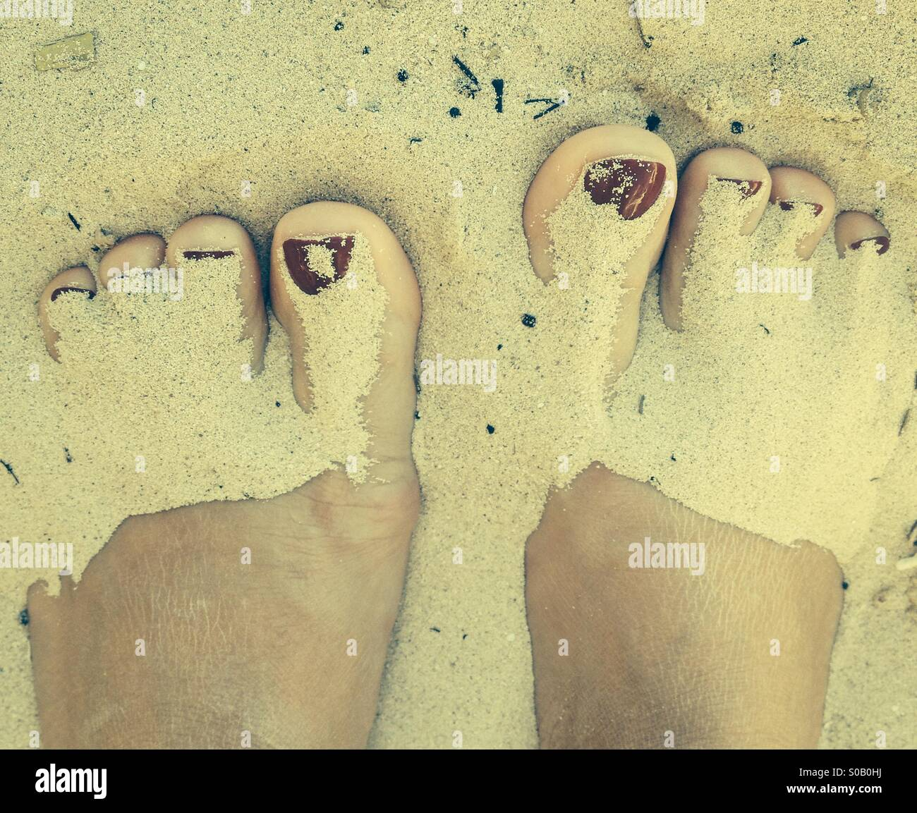 Feet in sand - Stock Image