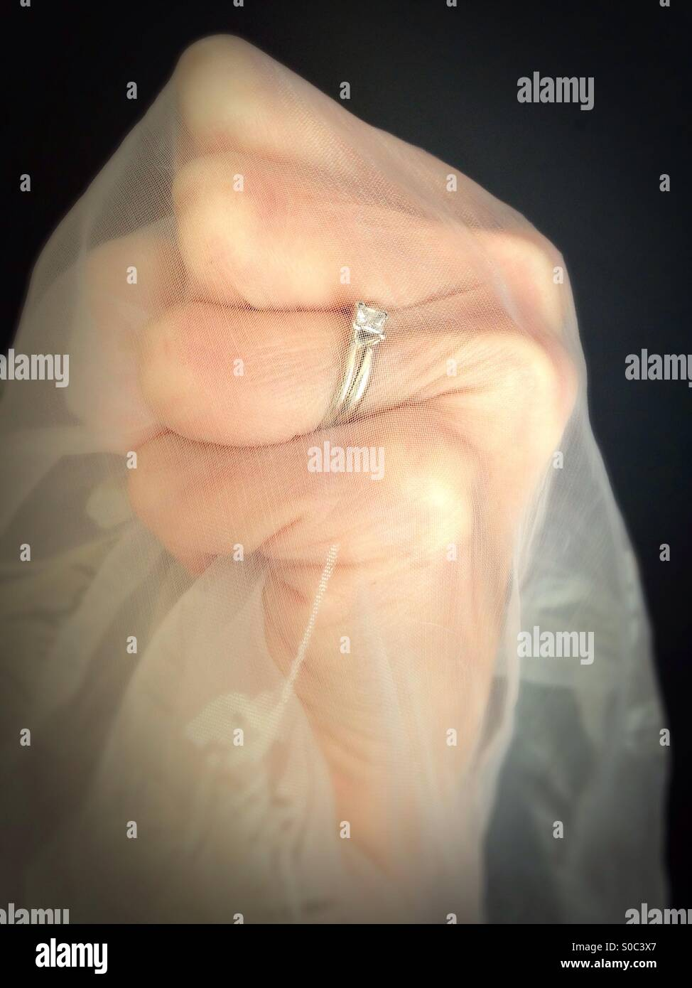 A tight fist wearing a wedding ring and gripping sheer gauzy fabric