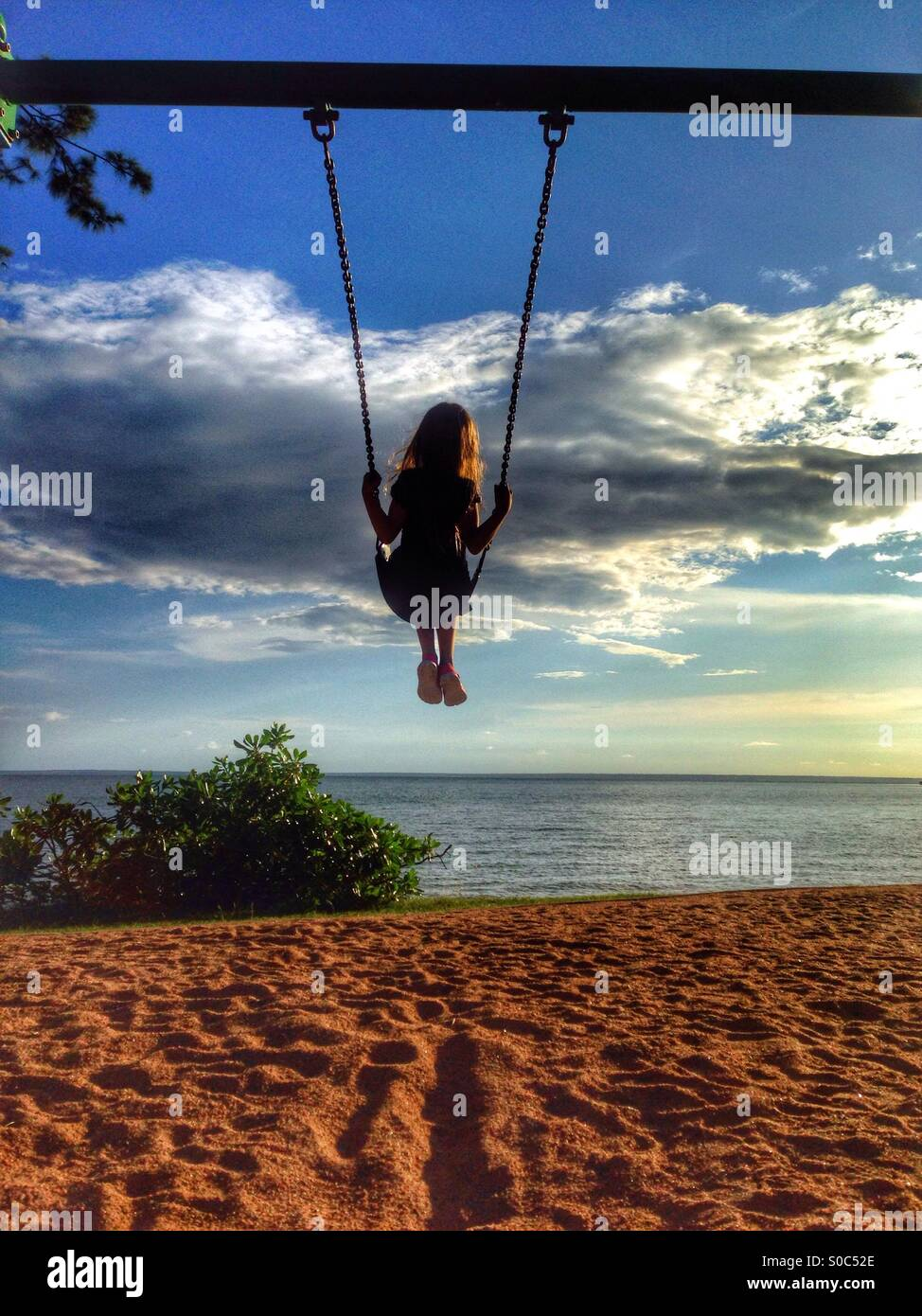 Young girl on a swing at the beach. - Stock Image