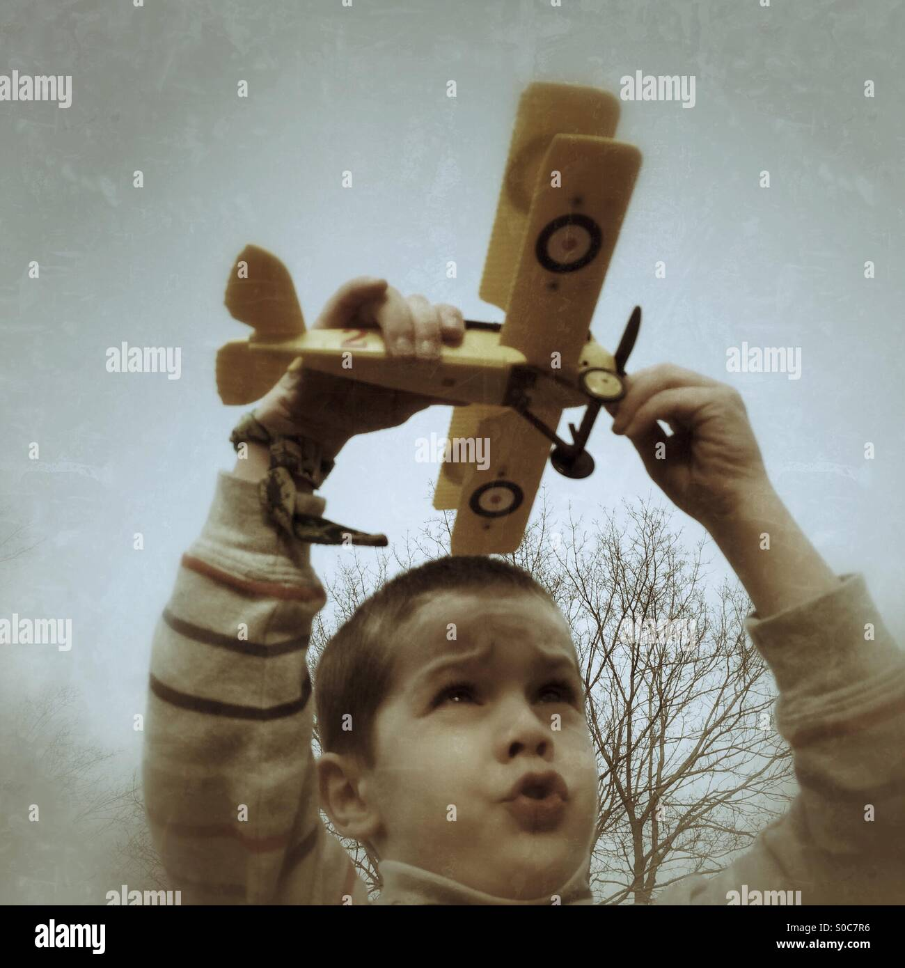 Young boy playing with model biplane - Stock Image