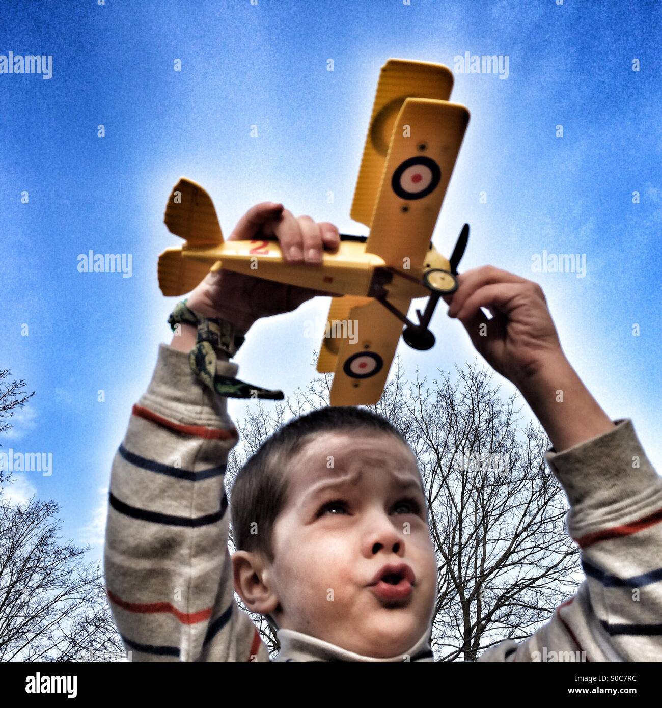 Young boy flying toy biplane - Stock Image