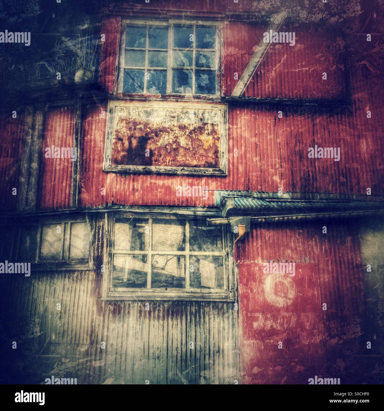 Grungy, rusting windows and corrugated metal wall of an old, abandoned, decrepit house doubling as a shop, with - Stock Image