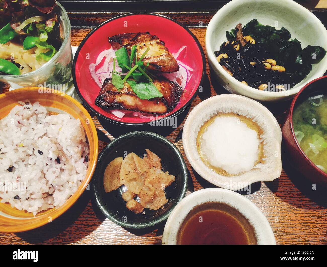Traditional, healthy Japanese lunch with fish, miso soup, beans, mixed grain rice, daikon oroshi or grated radish - Stock Image