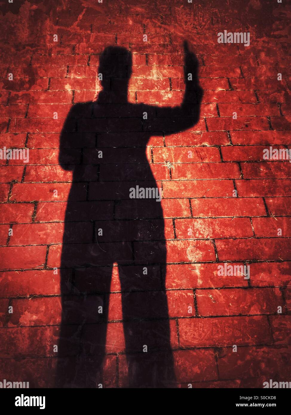 Shadow silhouette selfie of person pointing finger to the sky, over crimson brick pavement, with grunge texture - Stock Image