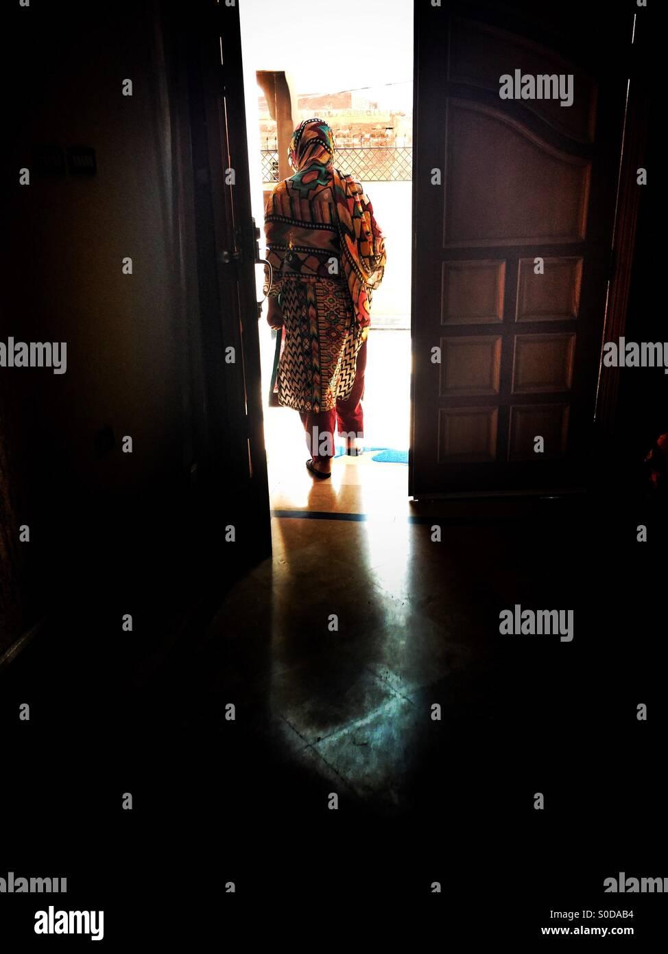Pakistani woman walking out the house - Stock Image
