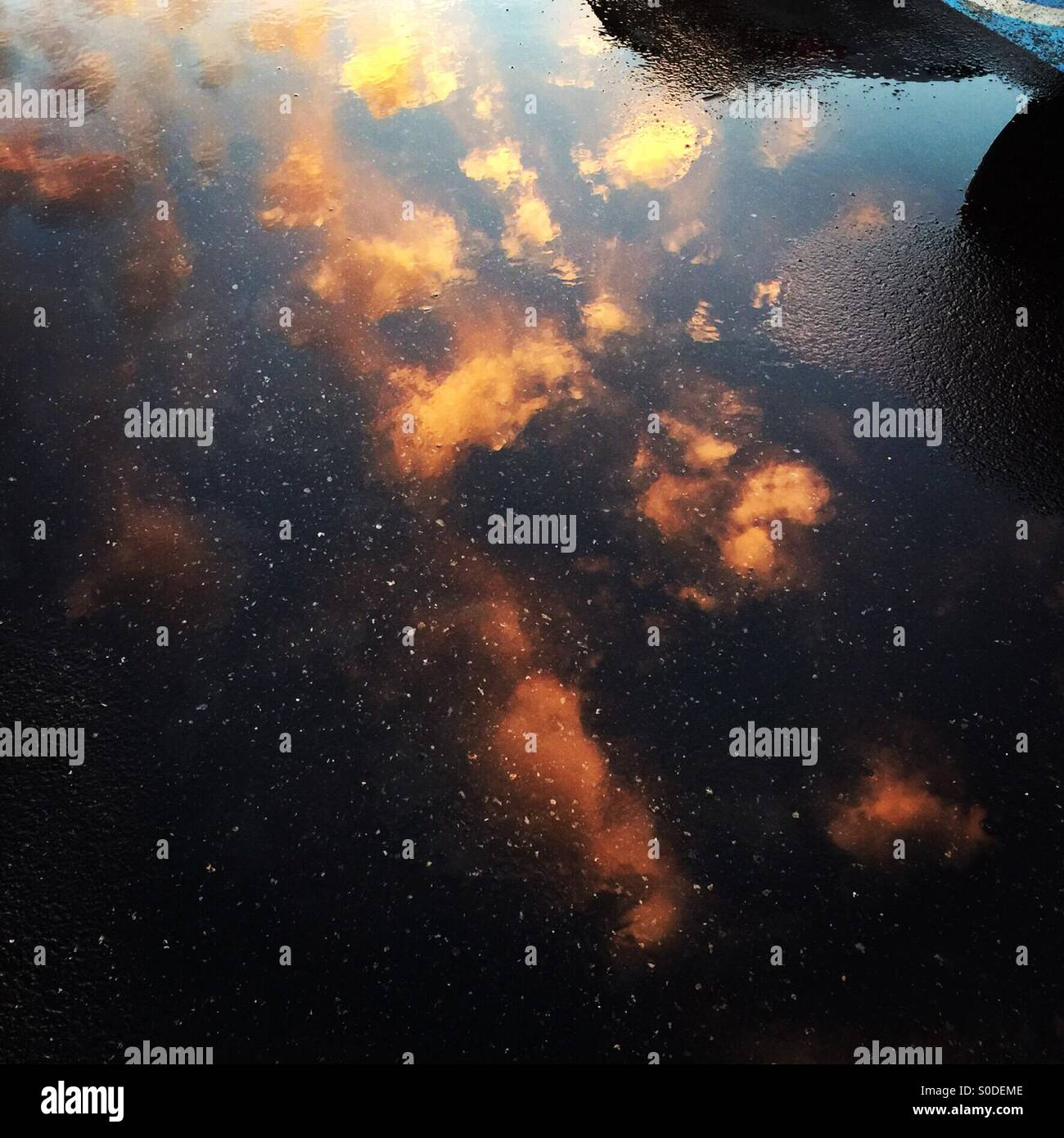 dramatic-clouds-reflected-in-a-parking-lot-puddle-S0DEME.jpg