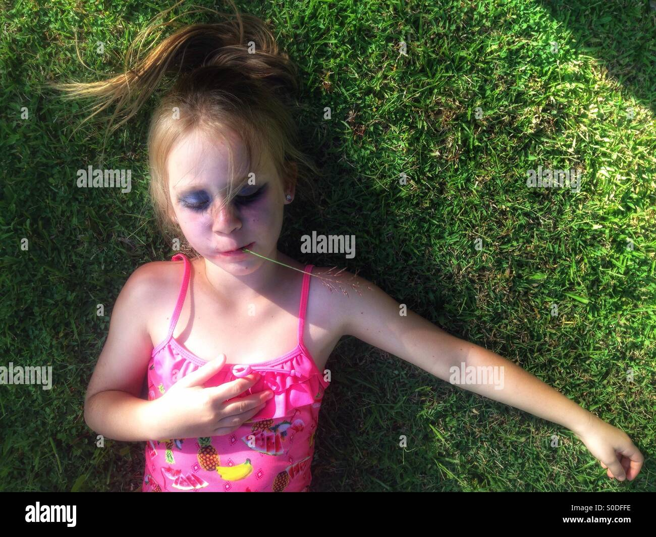 Little girl resting on the lawn. - Stock Image