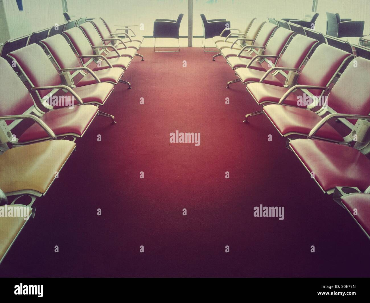 Empty chairs in waiting area at departure lounge within Terminal 1 of Charles de Gaulle international airport in - Stock Image