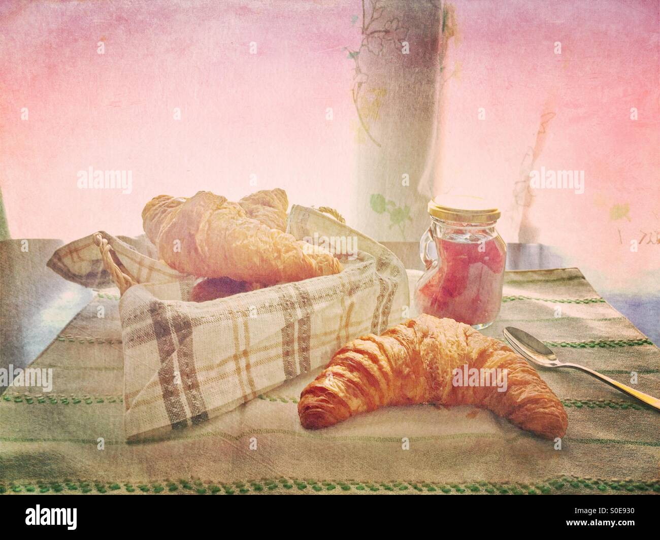 Small jar of homemade strawberry jam, bread basket with croissant, striped cloth and silver spoon. Vintage texture - Stock Image
