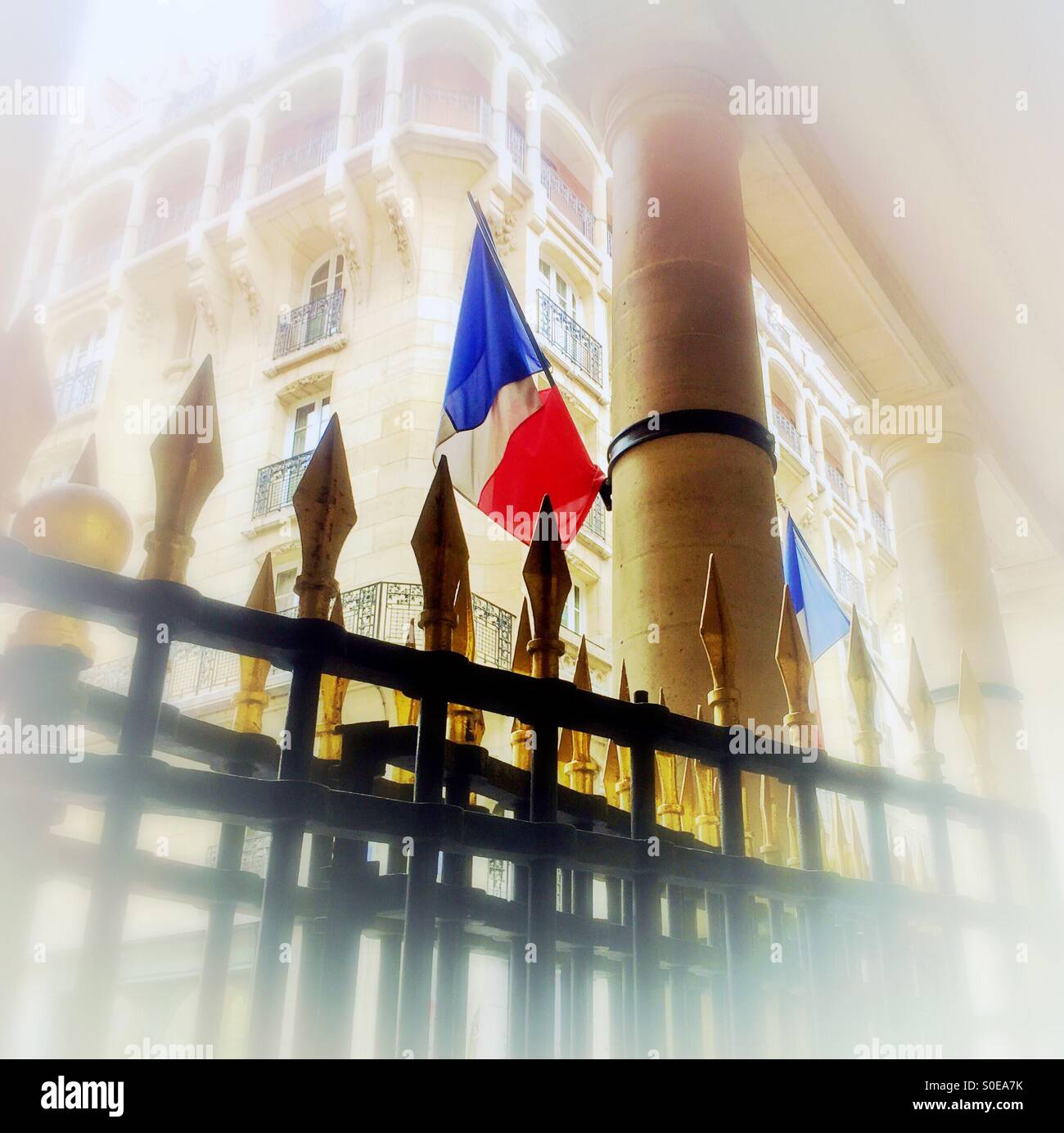 French flag on classic column with gold and black gate in foreground and beautiful traditional Parisian apartment - Stock Image