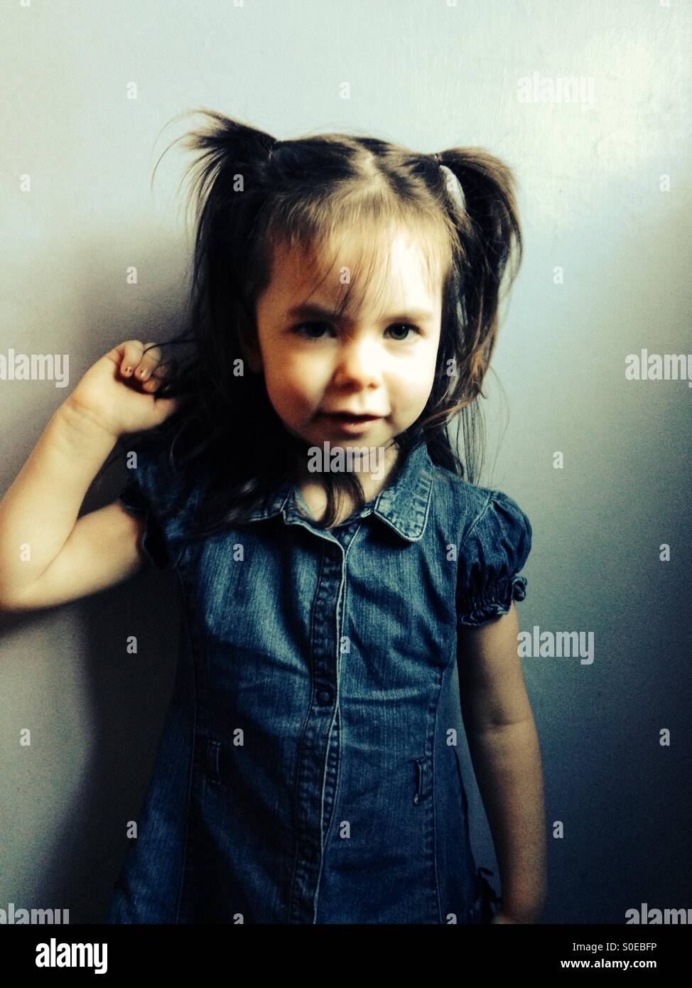 3-year old girl in denim dress and pigtails in her hair - Stock Image