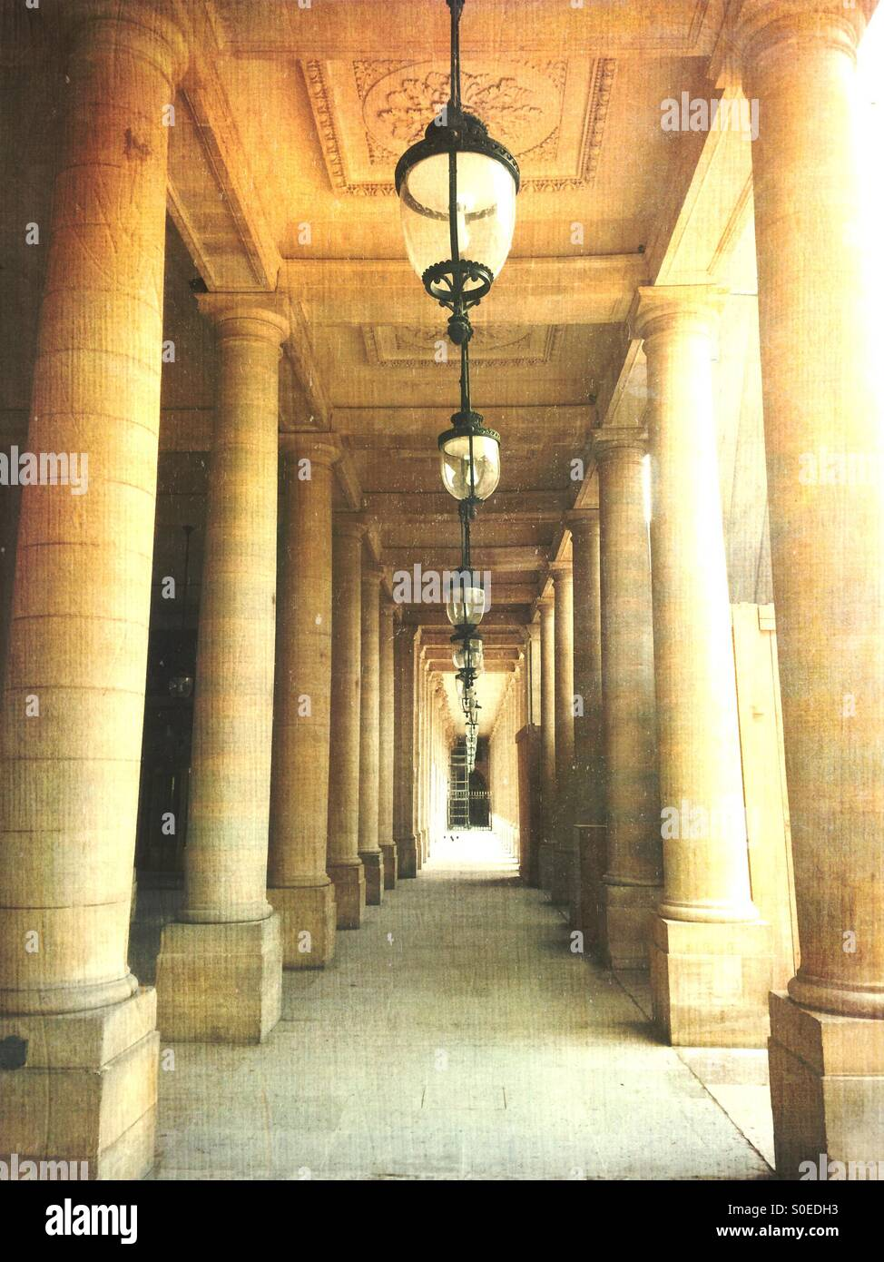 Beautiful classical columns and antique pendant ceiling lamps line the arcade of Valois Gallery at Palais-Royal. - Stock Image
