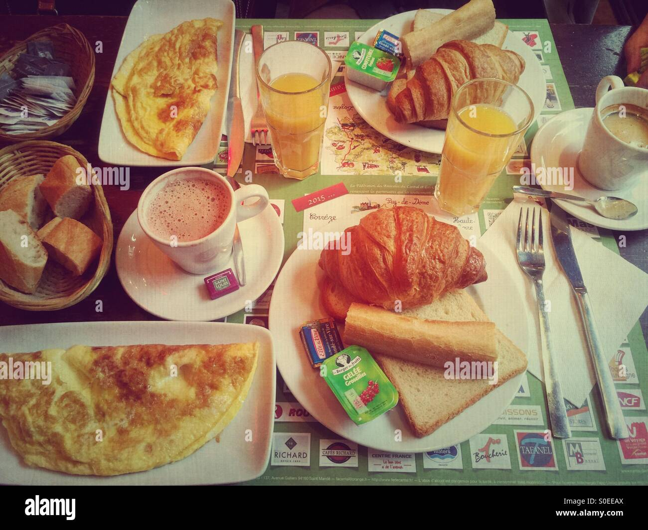 Typical French cafe breakfast at Le Musset brasserie in Paris, France. Croissant, coffee, hot chocolate, orange - Stock Image