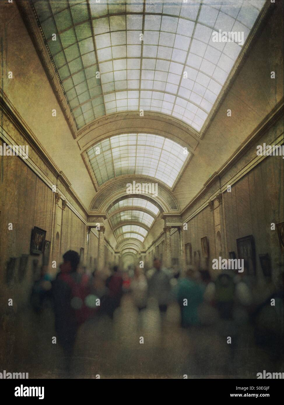 Crowd of tourists at the Grande Galerie or Grand Gallery in the Louvre museum in Paris, France. Vintage texture - Stock Image