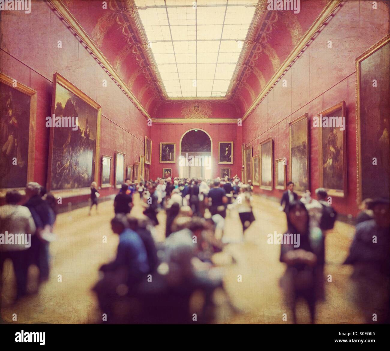 Crowd of tourists in the Red Room gallery at the Louvre museum in Paris, France. Vintage texture overlay. - Stock Image