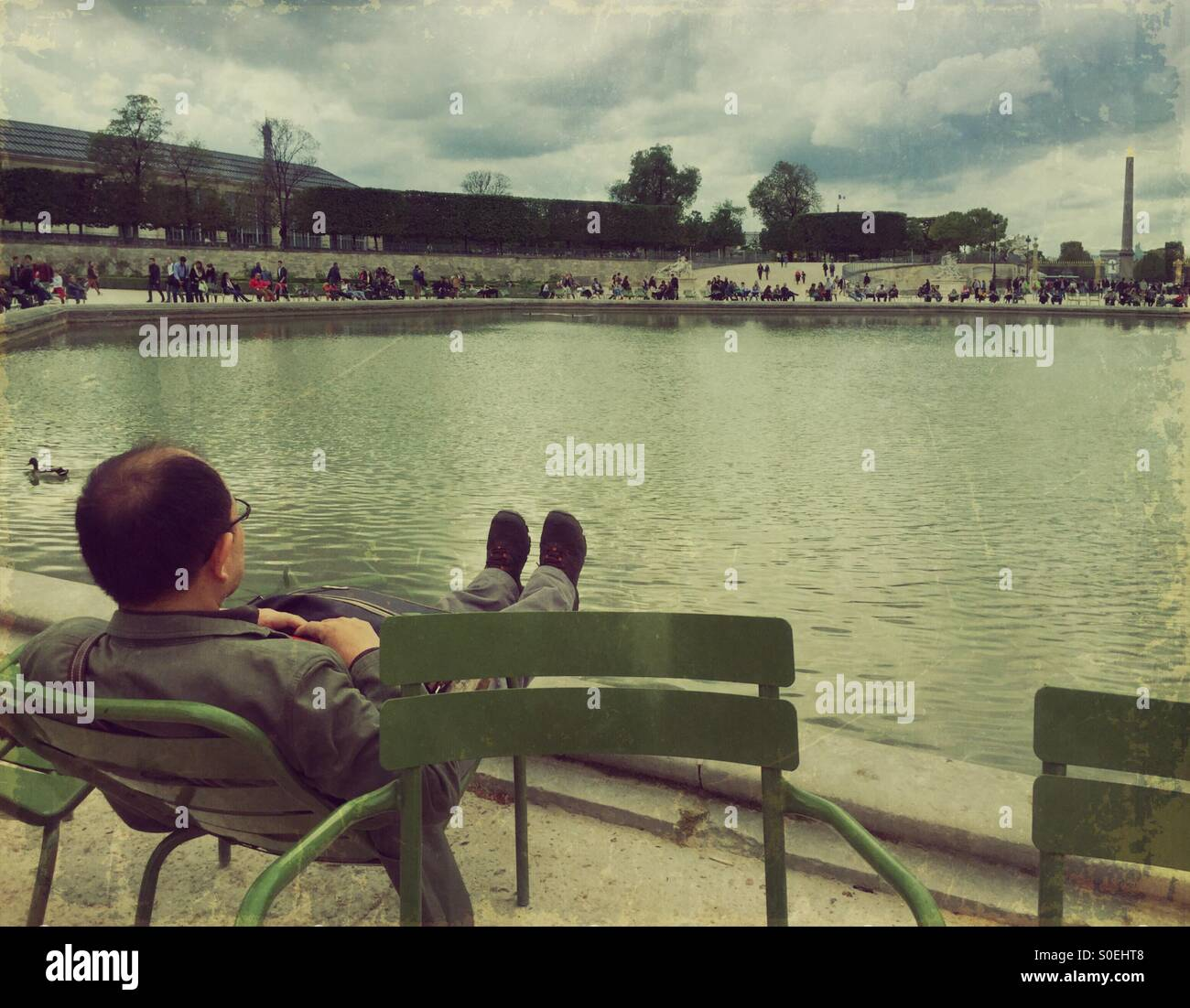 Man relaxing on a lawn chair by the Bassin Octagonal pond at Jardin des Tuileries garden in Paris, France. Vintage Stock Photo