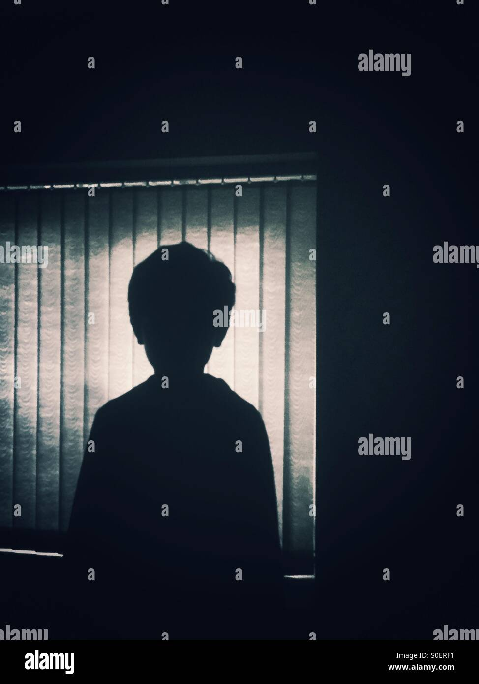 Silhouette of a little boy by the window - Stock Image
