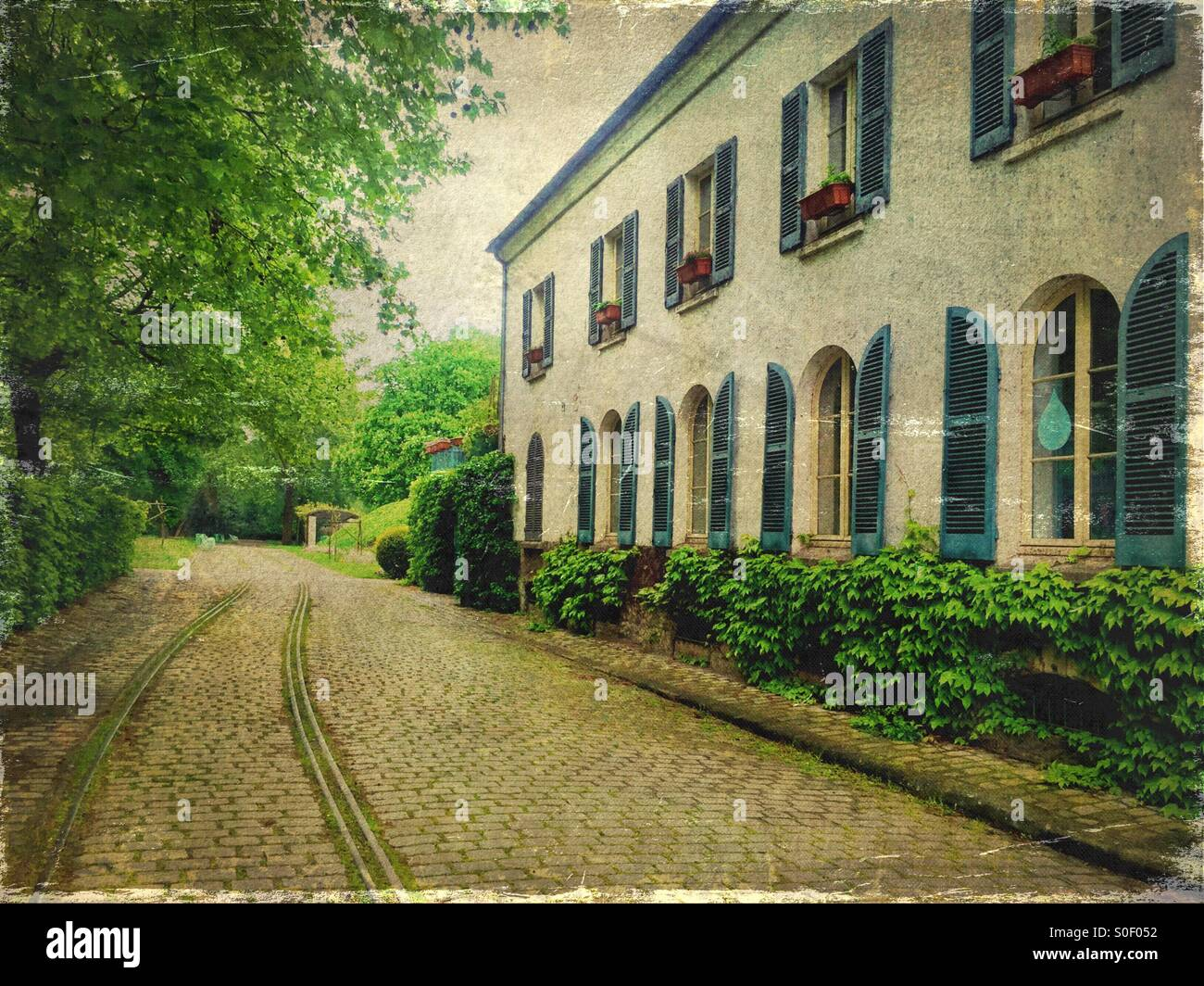 View of Maison du Jardinage with pretty blue shutters at Parc de Bercy in Paris, France. Brick pavement, trees and Stock Photo