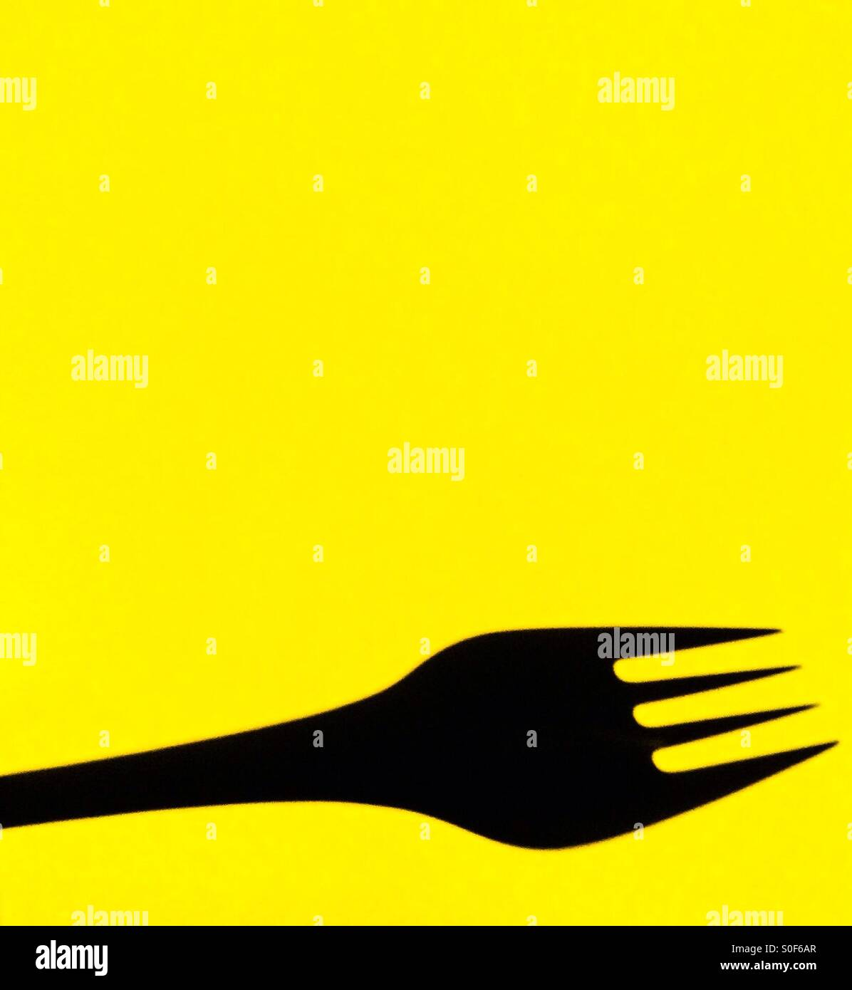 Fork on yellow background Stock Photo