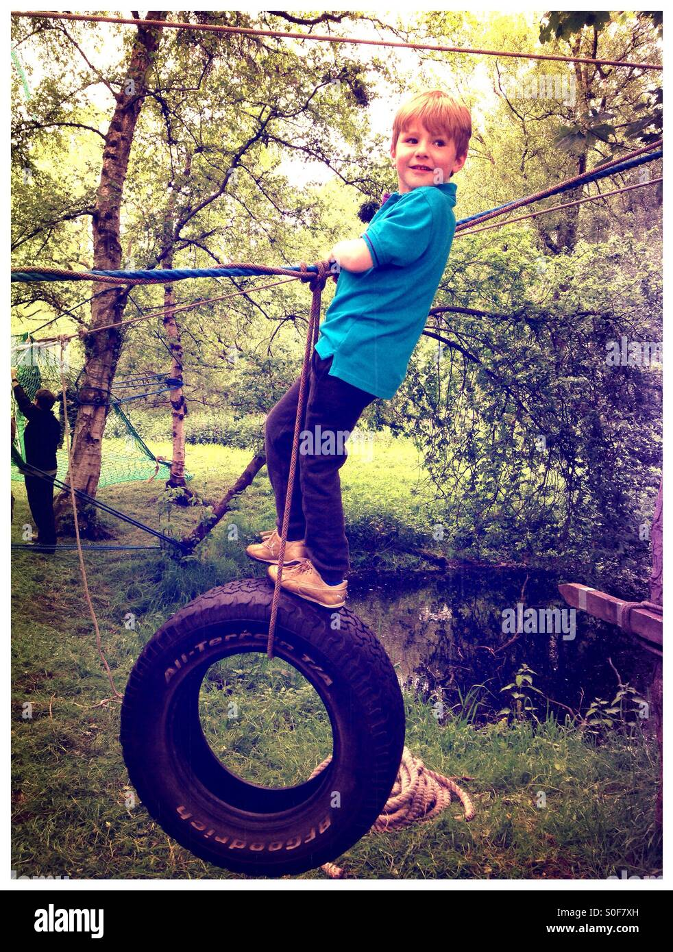 Boy swinging on a rope and tyre. Adventure course. Assault course. Woodland games - Stock Image