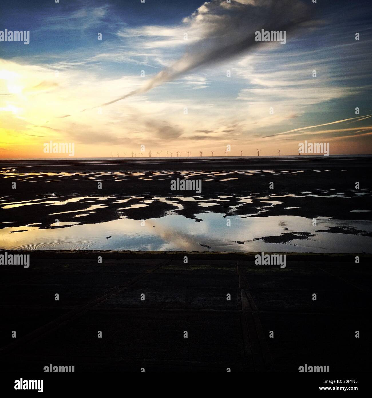 The Burbo Bank wind farm in Liverpool Bay, north west England, seen at sunset from the Wirral shoreline. - Stock Image