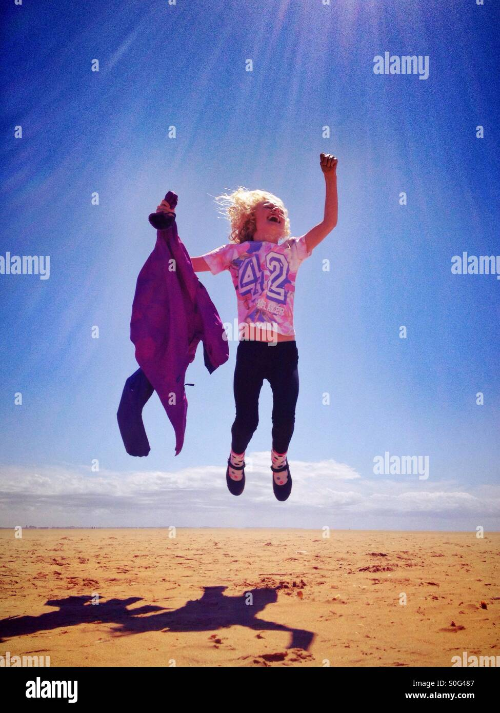 Young girl jumping for joy on beach - Stock Image