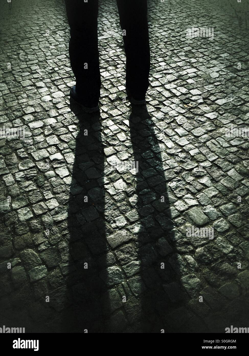 Man standing on cobbled road - Stock Image