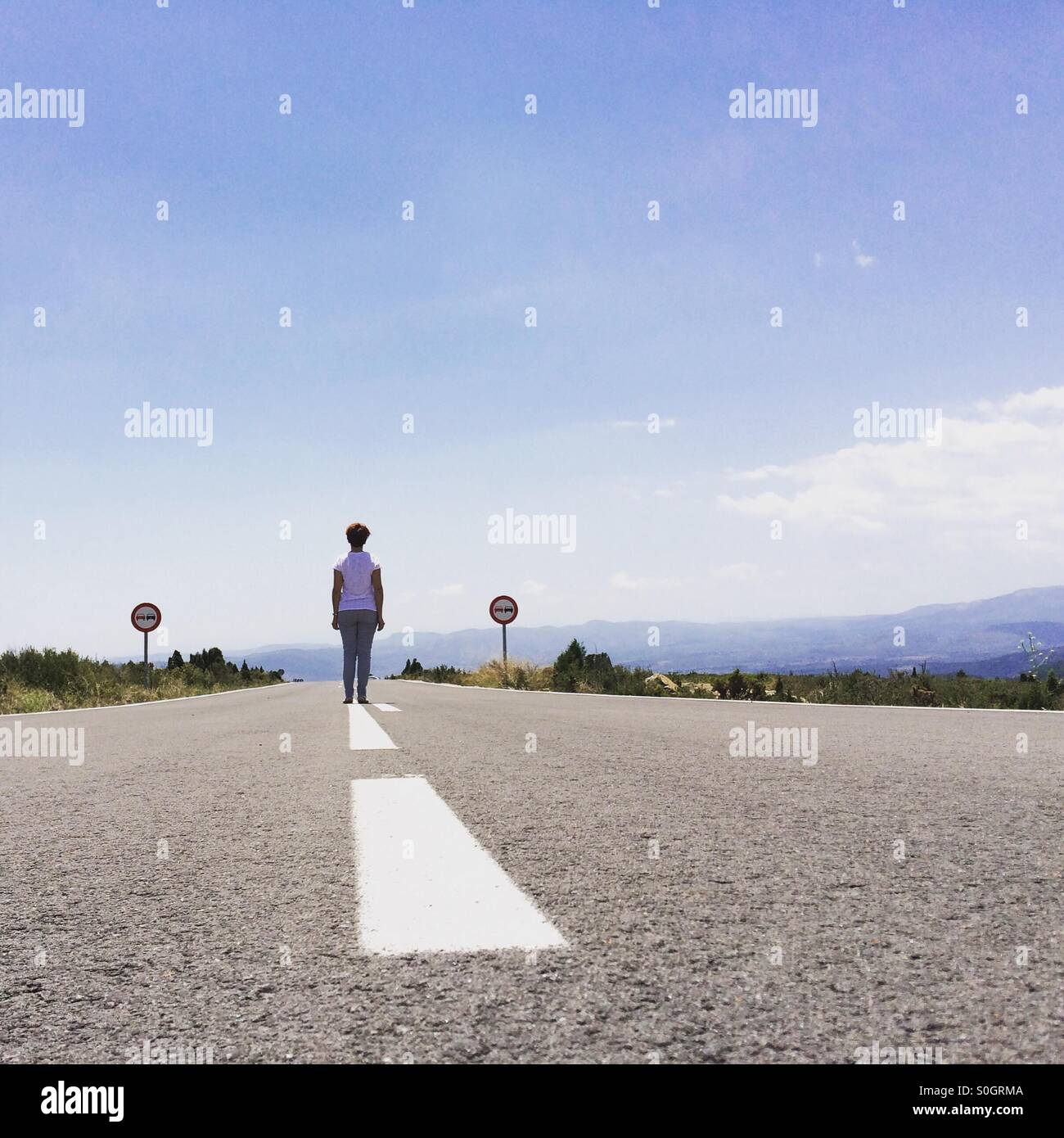 Woman on an empty road - Stock Image