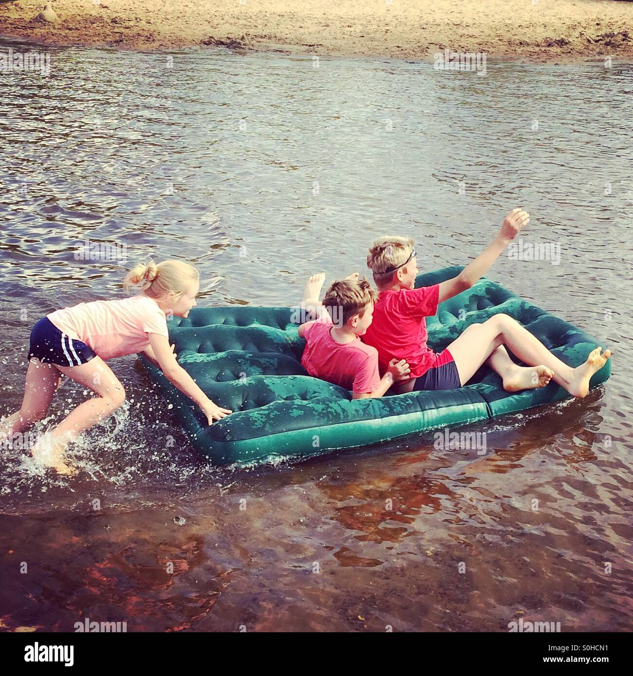 Children having fun on the river - Stock Image