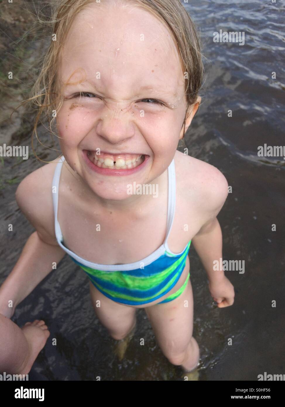 Young girl smiling and having fun grabbing her brother's leg in the river - Stock Image