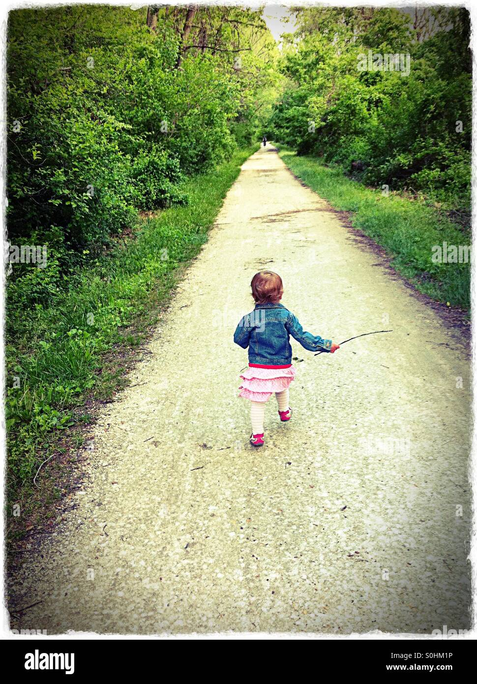 Toddler running down a rail trail in the spring - Stock Image