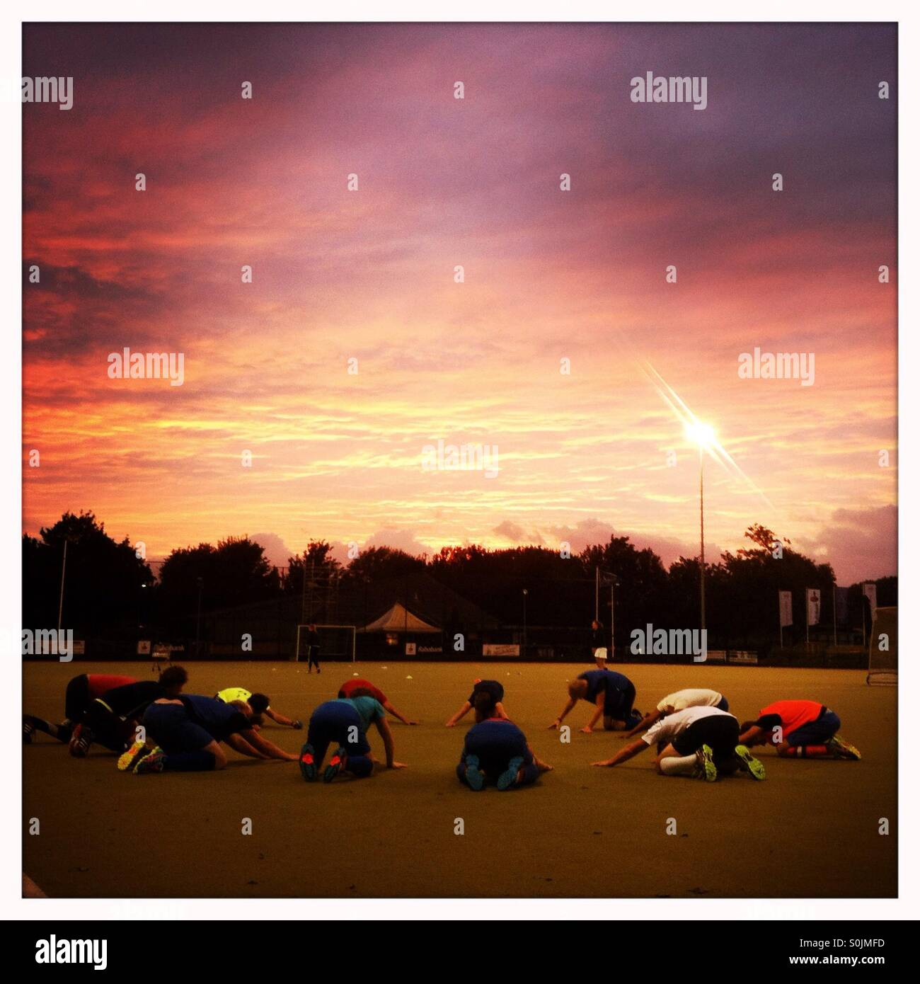 A hockey team doing a sports warming up exercise together in a circle with a dramatic red and purple sunset  and - Stock Image