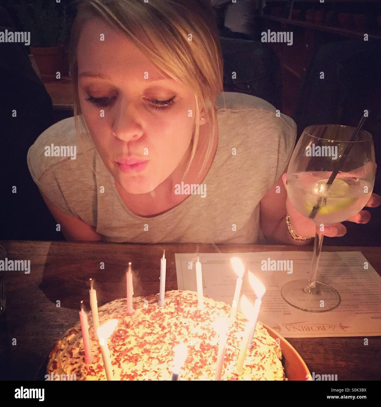 Girl blowing out candles - Stock Image