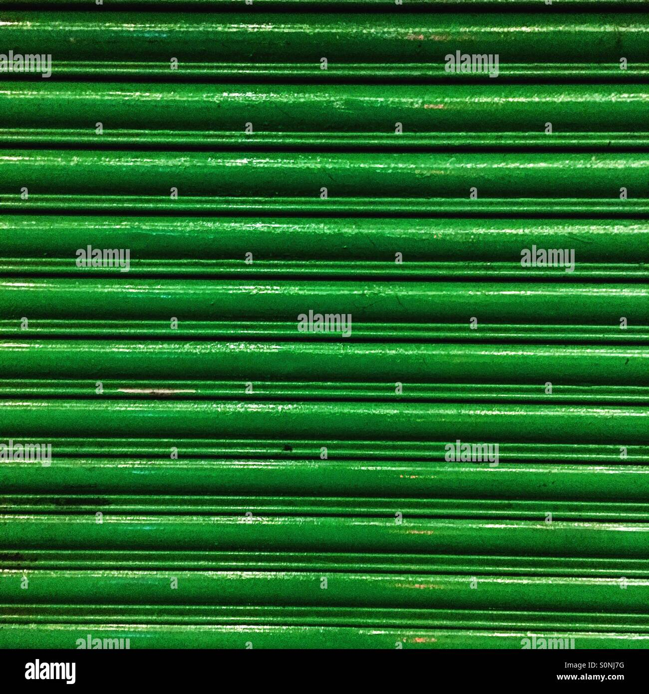 Bright green painted shop shutters. - Stock Image