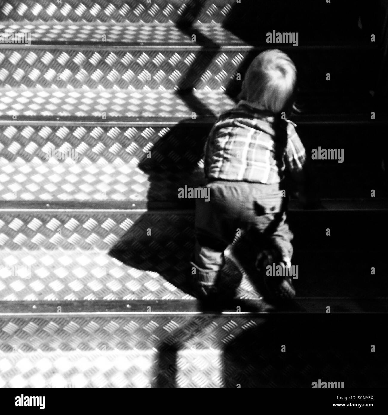 Boy toddler climbing stairs - Stock Image