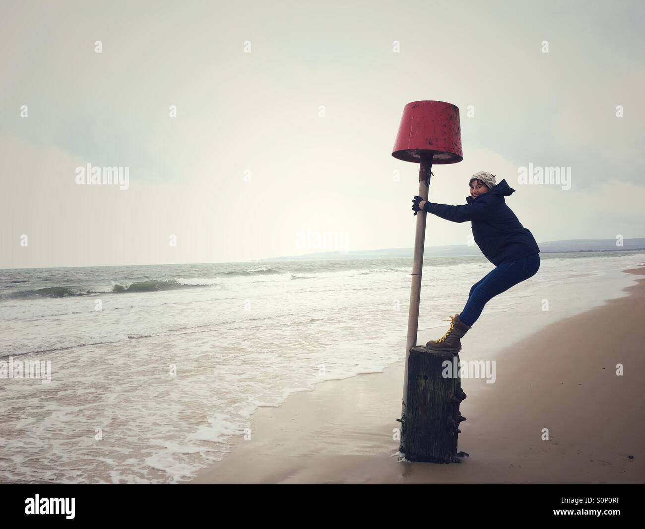 Woman having fun balancing on marker buoy on Dorset beach in winter - Stock Image