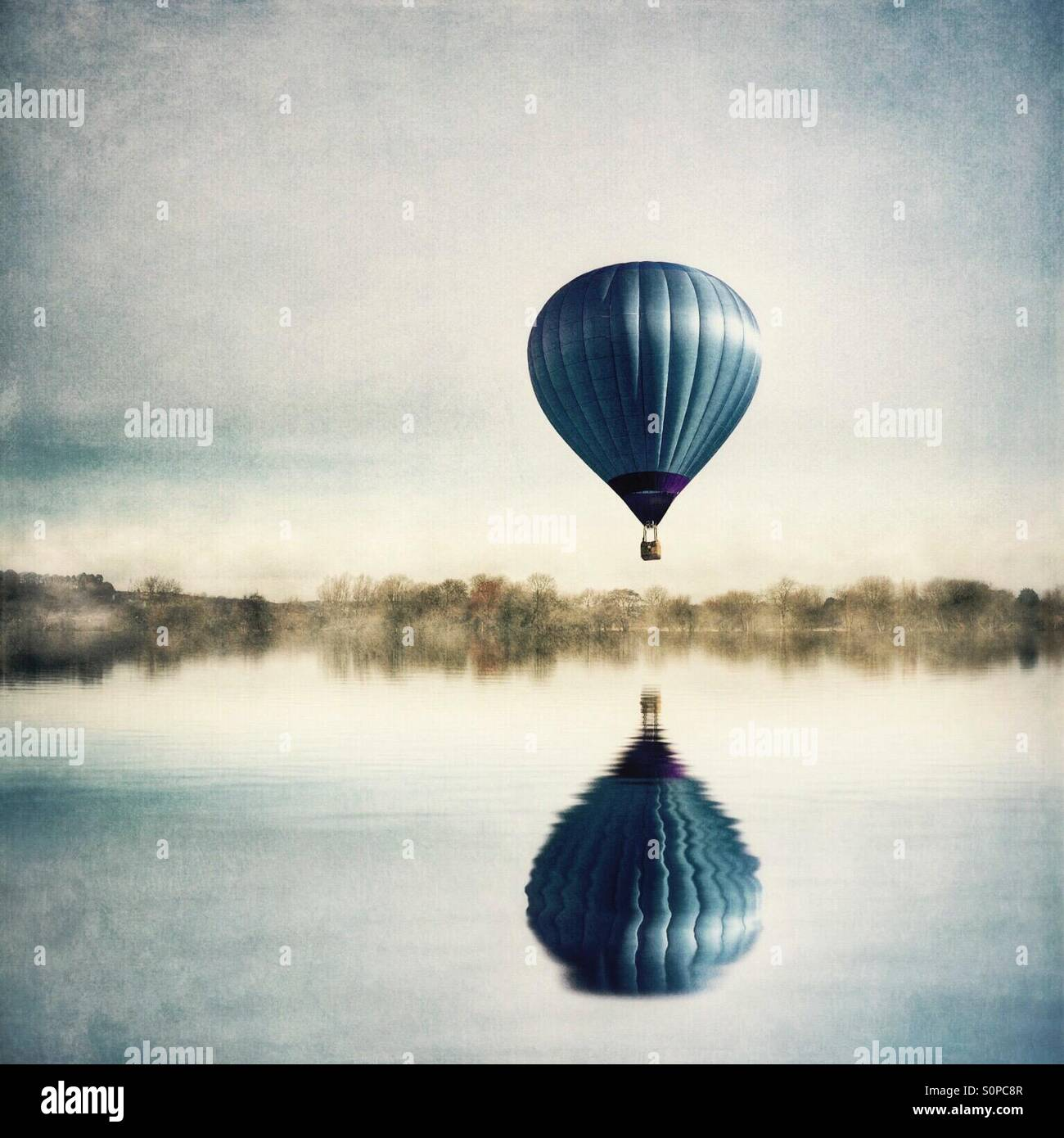 Reflection of hot air balloon in lake - Stock Image