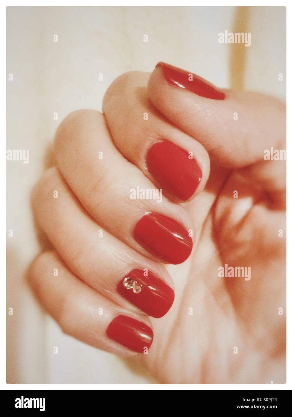 Red polished nails with 2 diamonds on the ring finger nail Stock ...