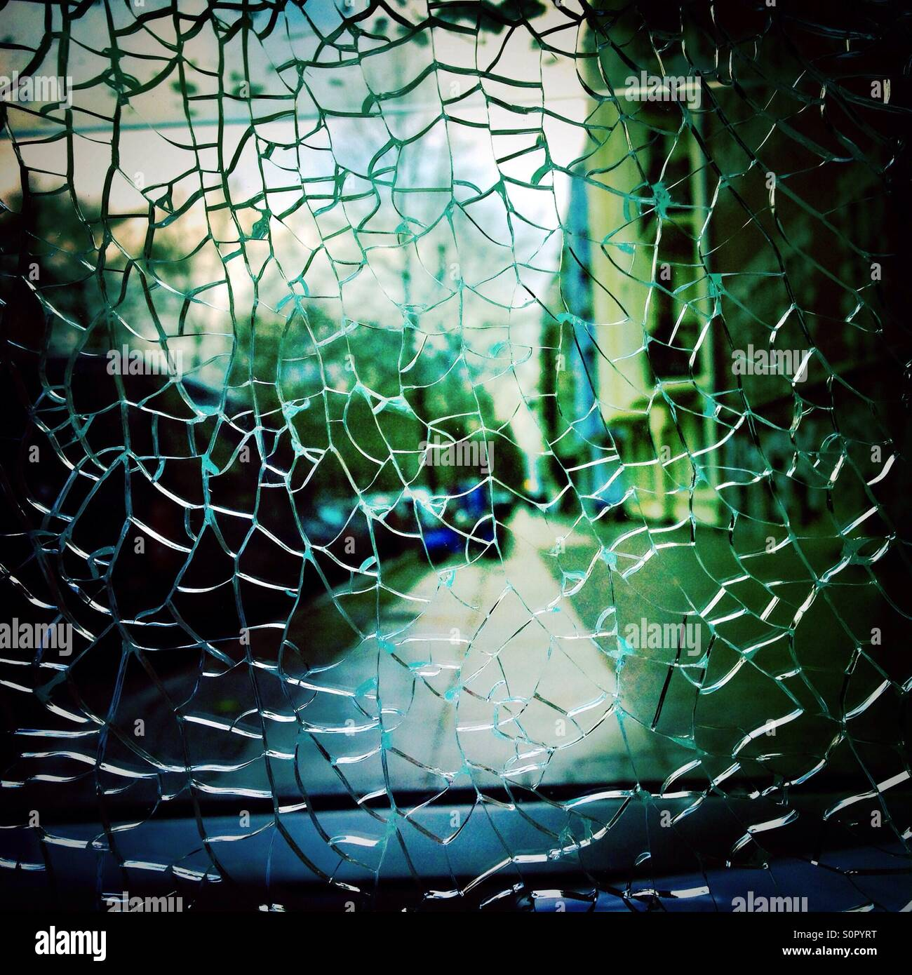 Broken Glass and a city street in the background - Stock Image