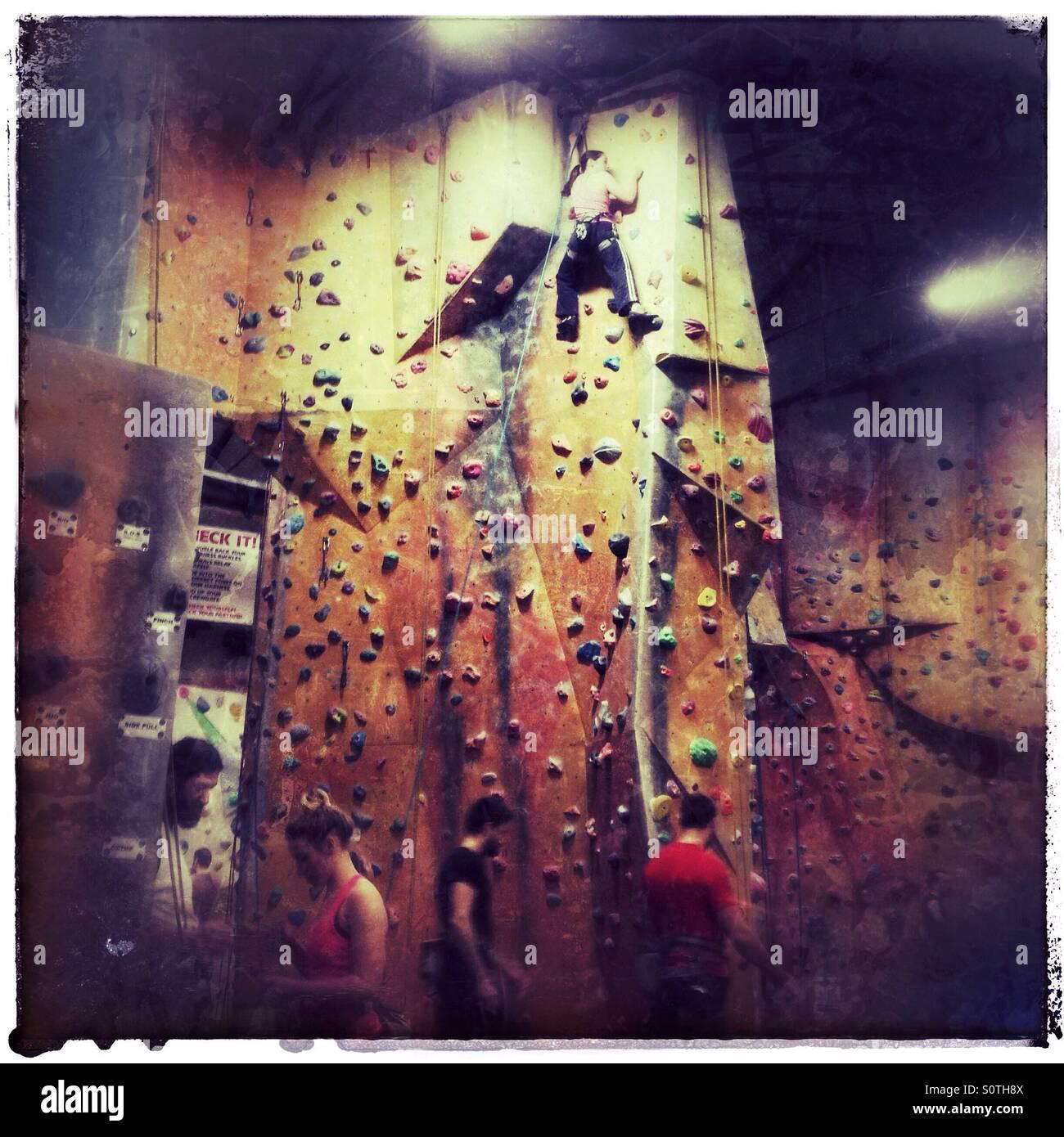 Pulling on plastic - Indoor rock climbing - Stock Image