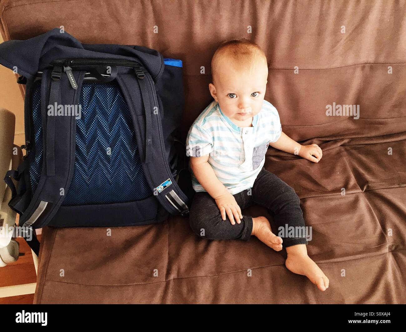 Cute little boy sitting on the couch - Stock Image