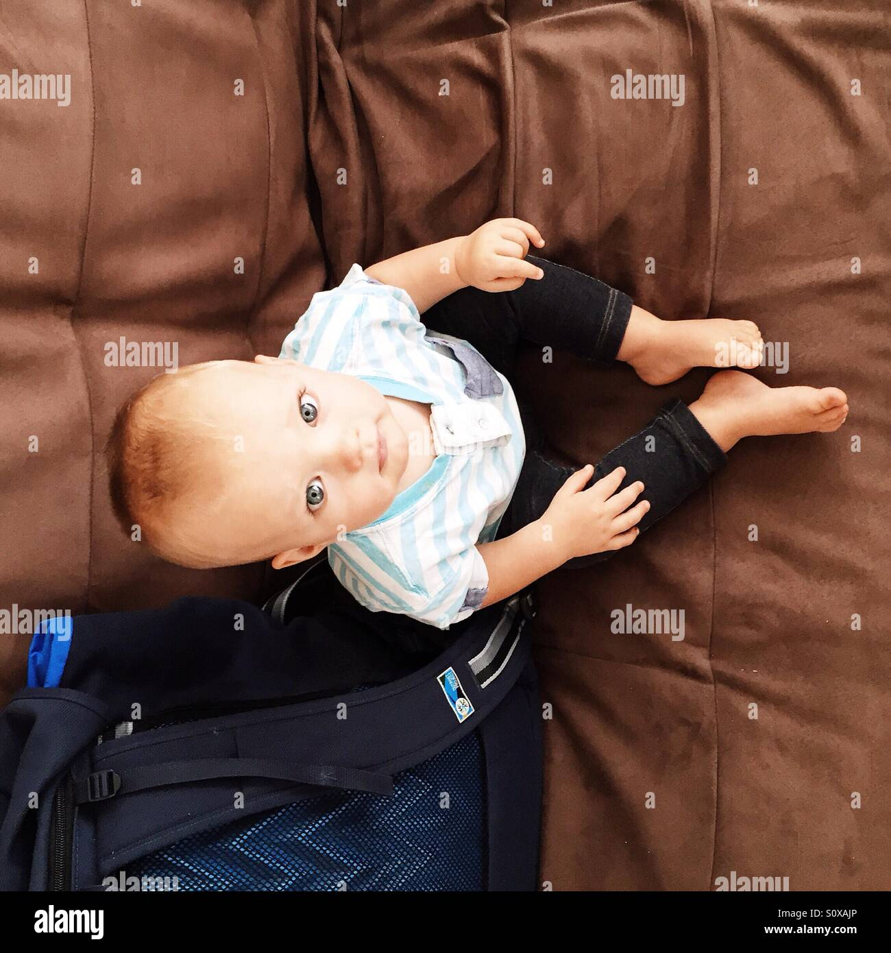 Little baby boy sitting on the couch - Stock Image