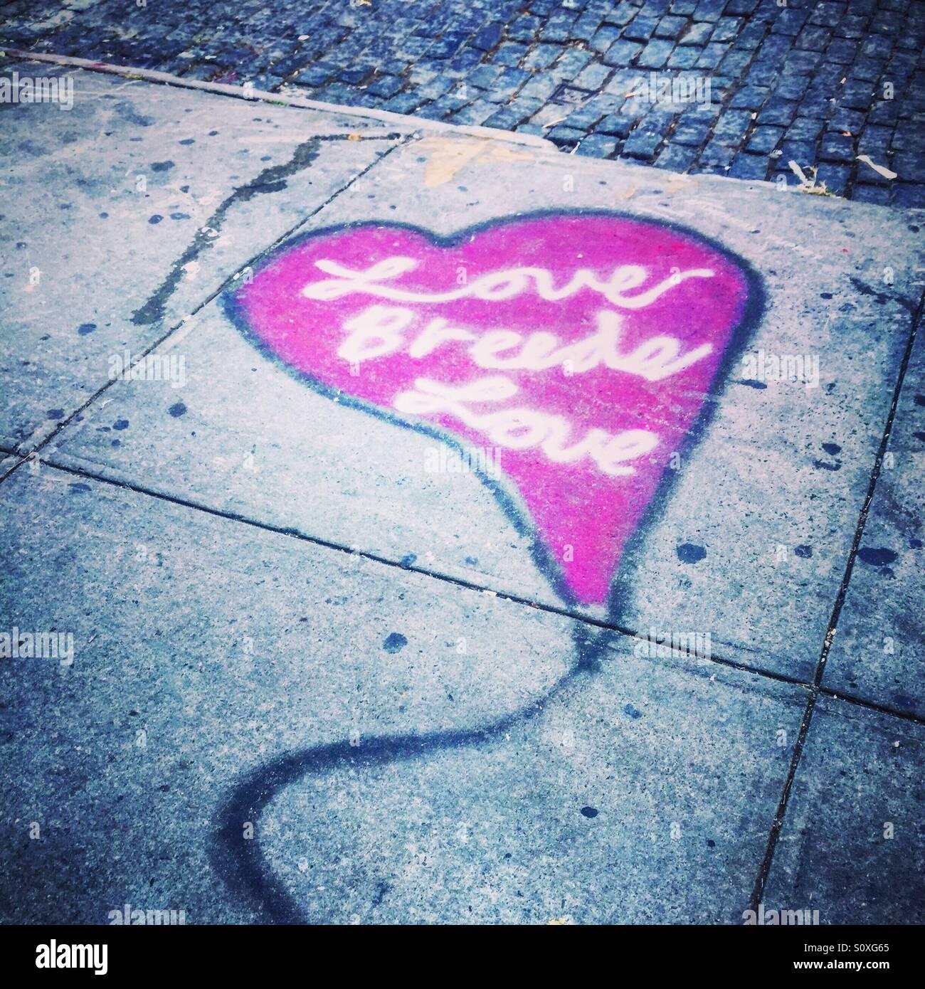 Love breeds love graffiti street art on pavement - Stock Image